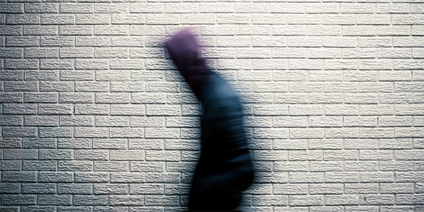 A blurred picture of a person walking past a wall