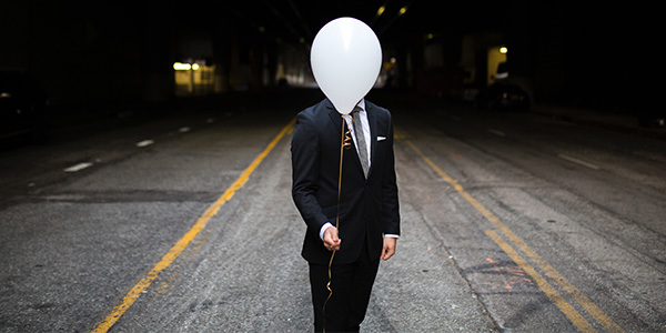 Man with ballon covering head